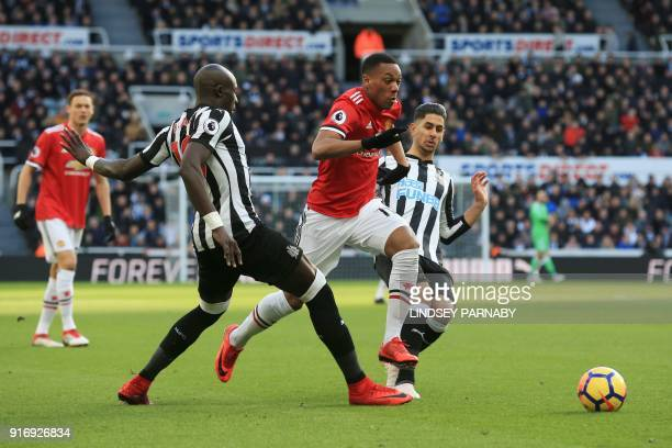 Manchester United's French striker Anthony Martial dribbles between Newcastle United's Senegalese midfielder Mohamed Diame and Newcastle United's...