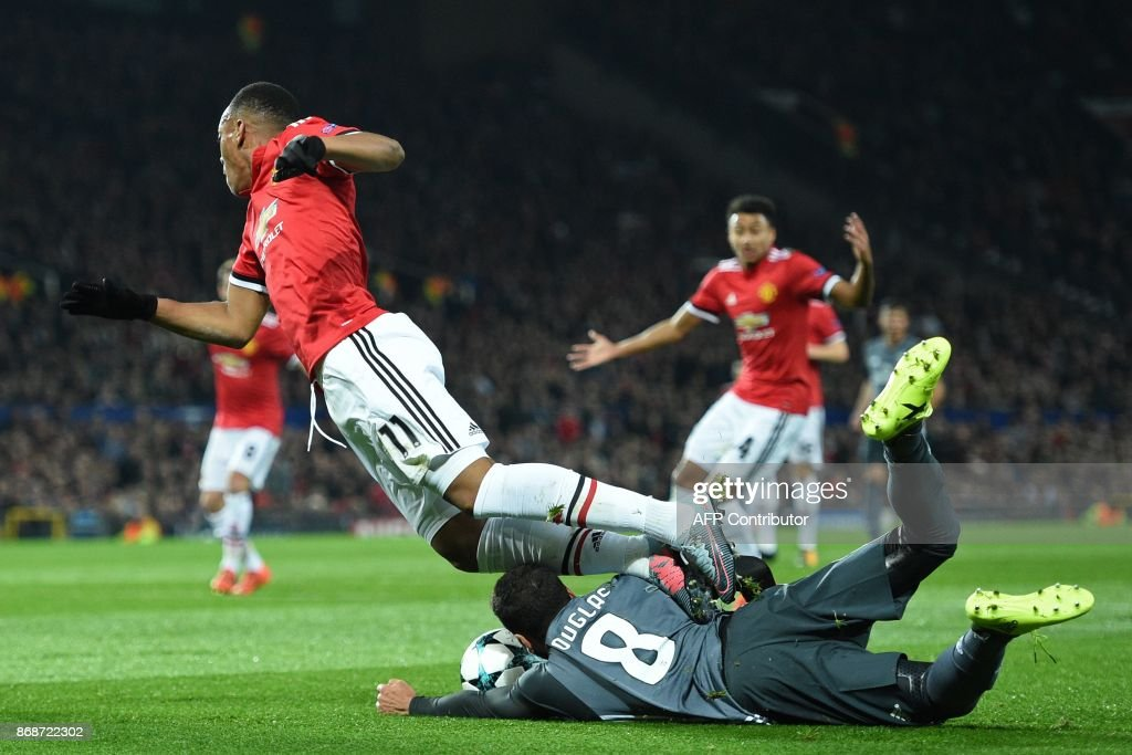 Manchester United's French striker Anthony Martial (L) goes down in the area, fouled by Benfica's Brazilian defender Douglas Pereira dos Santos for a penalty, during the UEFA Champions League Group A football match between Manchester United and Benfica at Old Trafford in Manchester, north west England on October 31, 2017. / AFP PHOTO / Oli SCARFF