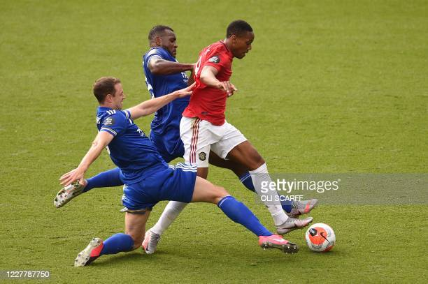 Manchester United's French striker Anthony Martial goes down under challenges from Leicester City's English-born Jamaican defender Wes Morgan and...