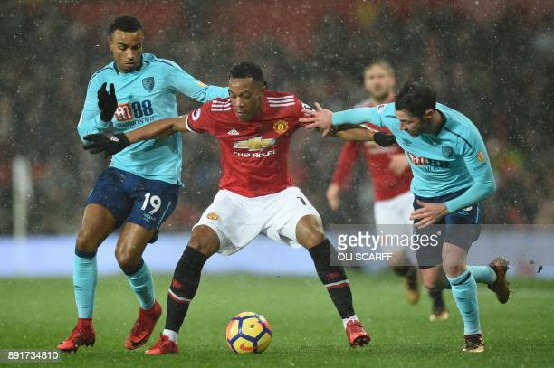 Manchester United's French striker Anthony Martial holds off Bournemouth's English midfielder Junior Stanislas and Bournemouth's English defender...