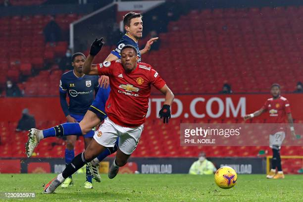 Manchester United's French striker Anthony Martial is fouled by Southampton's Polish defender Jan Bednarek for a penalty and red card for Bednarek...