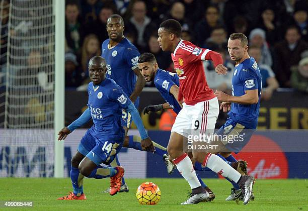 Manchester United's French striker Anthony Martial is marked by Leicester City's English midfielder Danny Drinkwater and Leicester City's French...