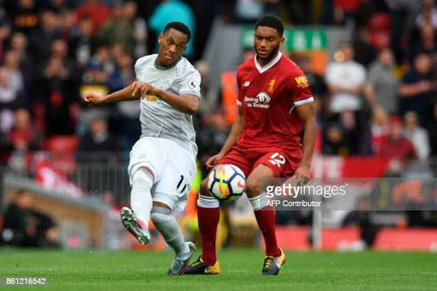 Manchester United's French striker Anthony Martial passes the ball past Liverpool's English defender Joe Gomez during the English Premier League...