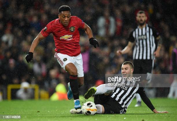 Manchester United's French striker Anthony Martial runs past a tackle from FK Partizan's Serbian defender Strahinja Pavlovic on his way to scoring...