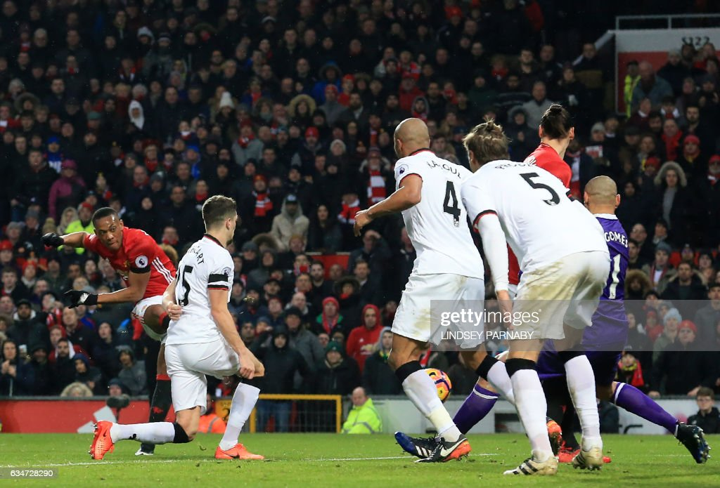 Manchester United's French striker Anthony Martial (L) scores their second goal during the English Premier League football match between Manchester United and Watford at Old Trafford in Manchester, north west England, on February 11, 2017. / AFP / Lindsey PARNABY / RESTRICTED TO EDITORIAL USE. No use with unauthorized audio, video, data, fixture lists, club/league logos or 'live' services. Online in-match use limited to 75 images, no video emulation. No use in betting, games or single club/league/player publications. /