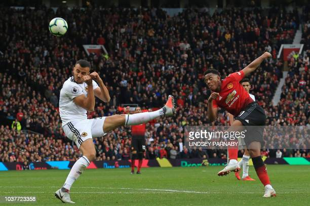 Manchester United's French striker Anthony Martial shoots past Wolverhampton Wanderers' Moroccan midfielder Romain Saiss during the English Premier...