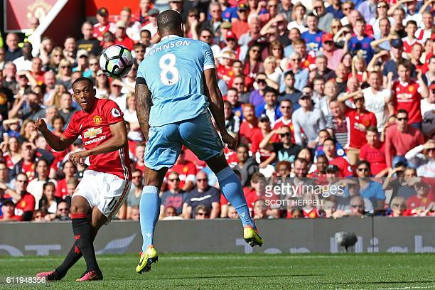 Manchester United's French striker Anthony Martial shoots to score the opening goal past Stoke City's English defender Glen Johnson during the...