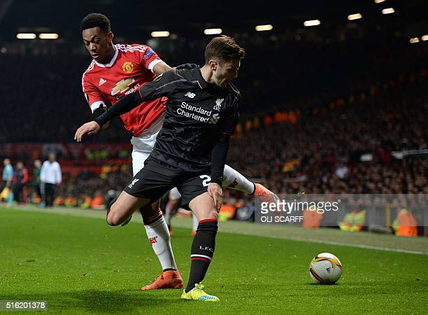 Manchester United's French striker Anthony Martial vies with Liverpool's English midfielder Adam Lallana during the UEFA Europa League round of 16...