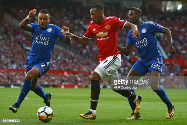 Manchester United's French striker Anthony Martial vies with Leicester City's English defender Danny Simpson and Leicester City's Nigerian midfielder...