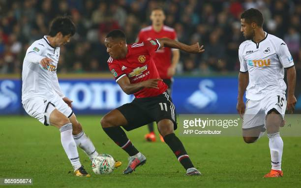 Manchester United's French striker Anthony Martial vies with Swansea City's South Korean midfielder Ki SungYueng and Swansea City's English...