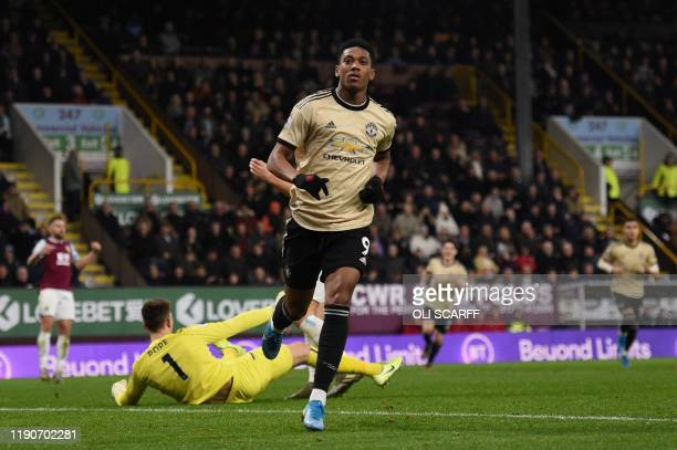 Manchester United's French striker Anthony Martial wheels away to celebrate scoring the opening goal during the English Premier League football match...