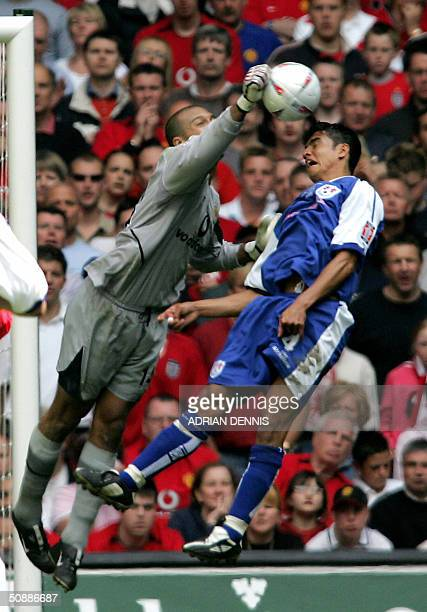 Manchester United's goalkeeper Tim Howard blocks an attempted shot by Millwall's Tim Cahill during their FA Cup Final football match 22 May 2004 in...