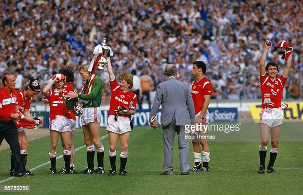 Manchester United's Gordon Strachan holds the trophy aloft as the players gather in front of the Royal Box for their lap of honour after beating...