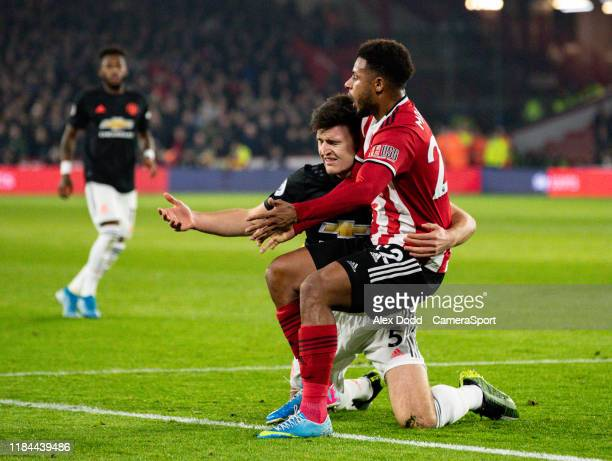 Manchester United's Harry Maguire grapples with Sheffield United's Lys Mousset during the Premier League match between Sheffield United and...