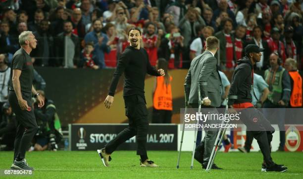 Manchester United's injured Swedish striker Zlatan Ibrahimovic enters the pitch after his team won the UEFA Europa League final football match Ajax...