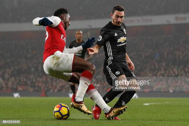 Manchester United's Italian defender Matteo Darmian vies with Arsenal's English striker Danny Welbeck during the English Premier League football...