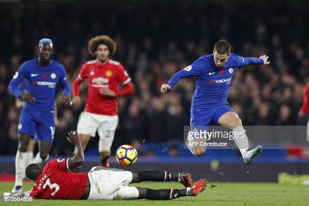 Manchester United's Ivorian defender Eric Bailly tackles Chelsea's Belgian midfielder Eden Hazard during the English Premier League football match...