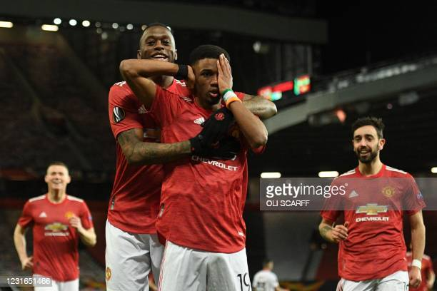 Manchester United's Ivorian midfielder Amad Diallo celebrates scoring the opening goal with Manchester United's English defender Aaron Wan-Bissaka...