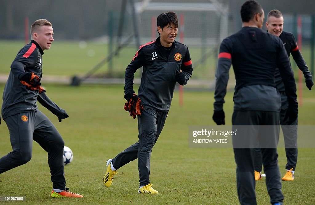 Manchester United's Japanese midfielder Shinji Kagawa (C) participates in a training session with Manchester United's Brazilian defender Rafael Da Silva (L) and Manchester United's English defender Chris Smalling at the Carrington training complex in Manchester, north-west England on February 12, 2013, on the eve of their UEFA Champions League first knockout round first leg football match against Real Madid in Madrid.