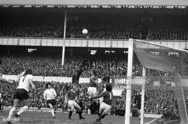 Manchester United's Jimmy Nicholl heads clear watched by teammates Alex Stepney and Brian Greenhoff and Tottenham Hotspur's Chris Jones and John...