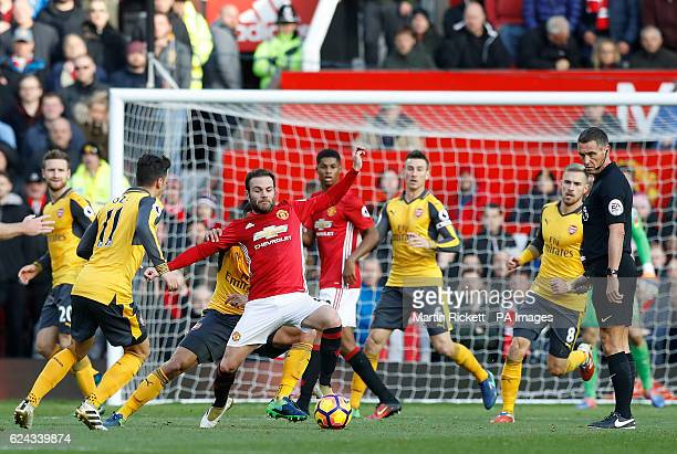 Manchester United's Juan Mata and Arsenal's Mesut Ozil battle for the ball during the Premier League match at Old Trafford Manchester