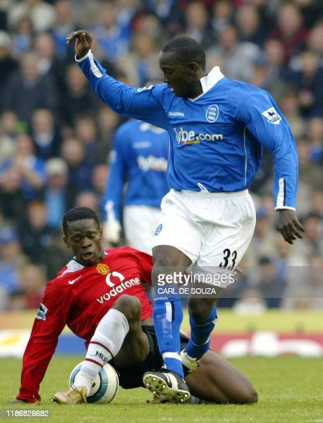 Manchester United's Louis Saha tackles Birmingham City's Dwight Yorke during their Premiership football match 16 October 2004 at Birmingham United...