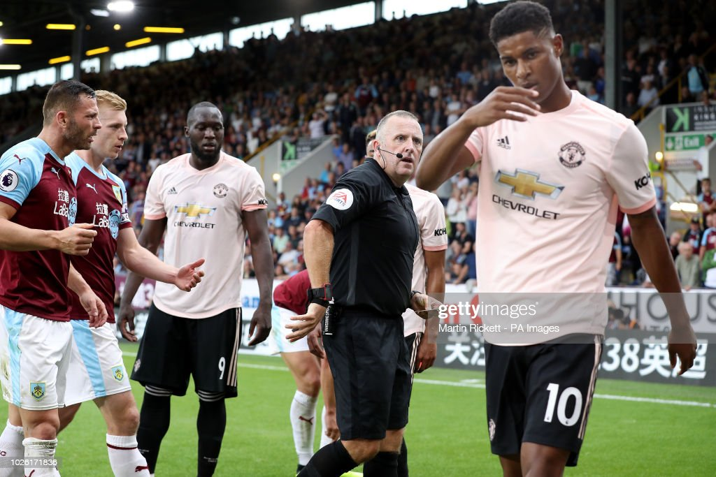 Manchester United's Marcus Rashford (right) is shown a red card by referee Jonathan Moss during the Premier League match at Turf Moor, Burnley.