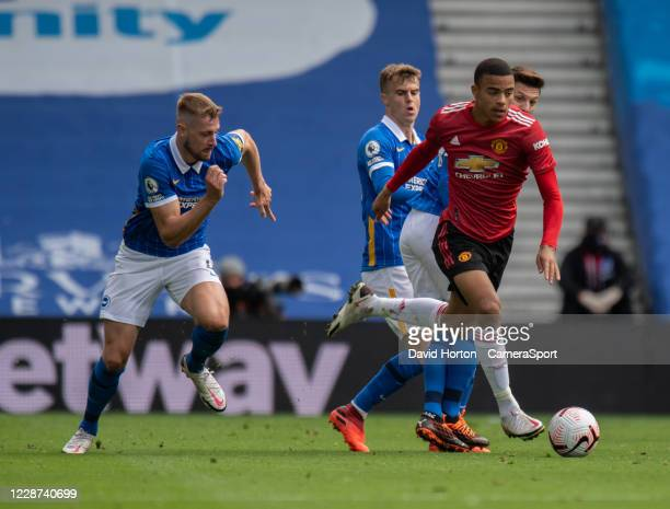 Manchester United's Mason Greenwood holds off the challenge from Brighton Hove Albion's Adam Webster during the Premier League match between Brighton...