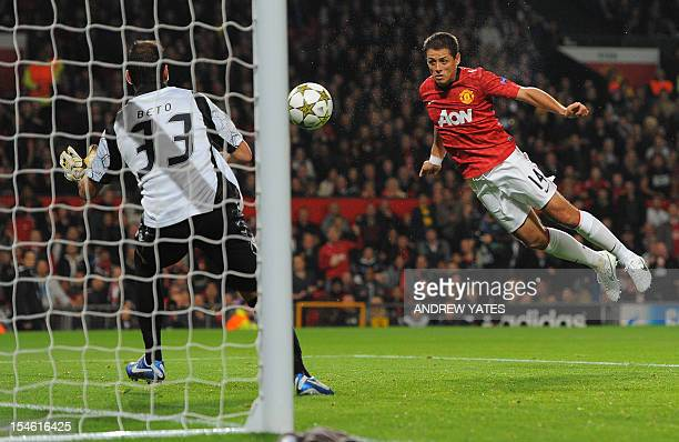 Manchester United's Mexican forward Javier Hernandez scores past SC Braga's Portuguese goalkeeper Beto during the UEFA Champions League group H...