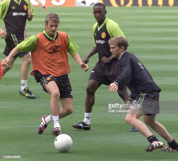 Manchester United's midfielder David Beckham fights for the ball with midfielder Jesper Blomqvist as forward Dwight Yorke looks on during the team's...