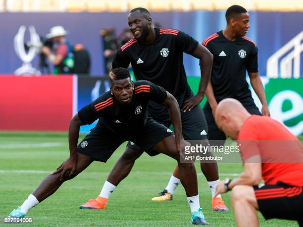 Manchester United's midfielder Paul Pogba and forward Romelu Lukaku stretch as they warm up during a training session ahead of the UEFA Super Cup...
