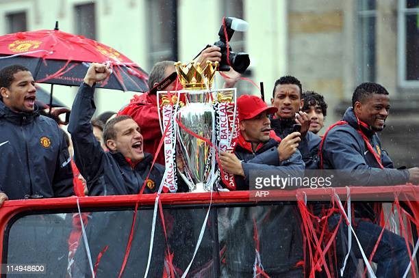 Manchester United's Nemanja Vidic and Rio Ferdinand hold the Premier League Trophy at the start of a bus parade carrying the players and officials...