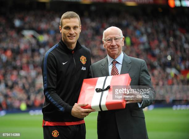 Manchester United's Nemanja Vidic is presented with a gift ahead of his final home game for the club by Sir Bobby Charlton