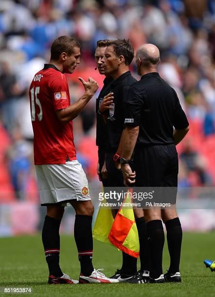 Manchester United's Nemanja Vidic speaks with match referee Mark Clattenburg