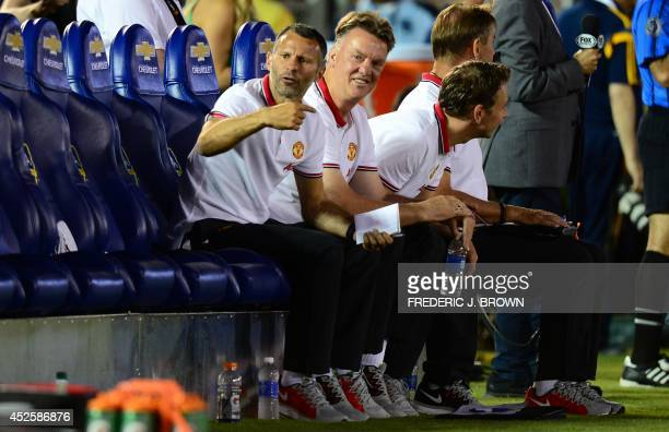 Manchester United's new coach Louis Van Gall and assistant Ryan Giggs follow the action from the bench against the LA Galaxy during their Chevrolet...