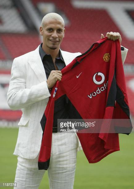 Manchester United's new signing Rio Ferdinand shows off his new shirt at a press conference at Old Trafford Manchester England on July 22 2002