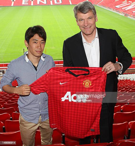 Manchester United's new signing Shinji Kagawa from Borussia Dortmund poses with Manchester United's Chief Executive David Gill at Old Trafford on...