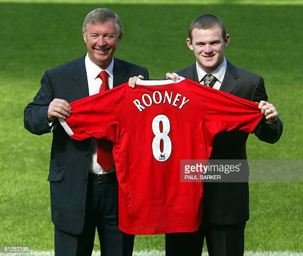 Manchester United's new signing Wayne Rooney holds his new jersey with manager Alex Furguson , 01 September 2004, at today's press conference after...