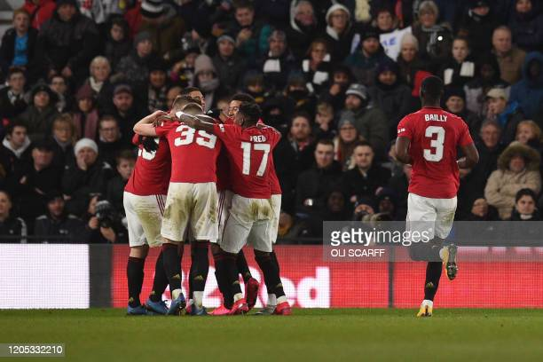 Manchester United's Nigerian striker Odion Ighalo celebrates scoring his team's third goal with his teammates during the English FA Cup fifth round...