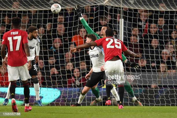 Manchester United's Nigerian striker Odion Ighalo scores his team's third goal during the English FA Cup fifth round football match between Derby...