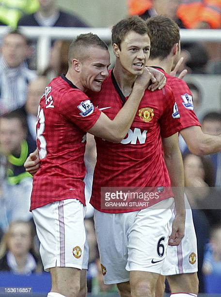 Manchester United's Northern Irish defender Jonny Evans celebrates with English midfielder Tom Cleverley after scoring their opening goal of the...