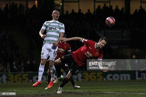 Manchester United's Northern Irish defender Jonny Evans heads a cross away that was otherwise destined for Yeovil Town's English striker Kieffer...