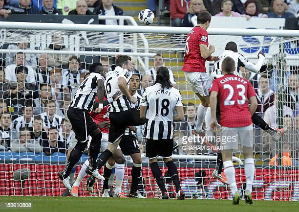 Manchester United's Northern Irish defender Jonny Evans scores the opening goal of the English Premier League football match between Newcastle United...
