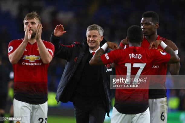 Manchester United's Norwegian caretaker manager Ole Gunnar Solskjaer celebrates with his players on the pitch after the English Premier League...