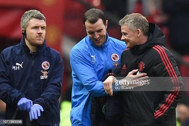 Manchester United's Norwegian caretaker manager Ole Gunnar Solskjaer greets Reading's Irish defender and former Manchester United player John O'Shea...