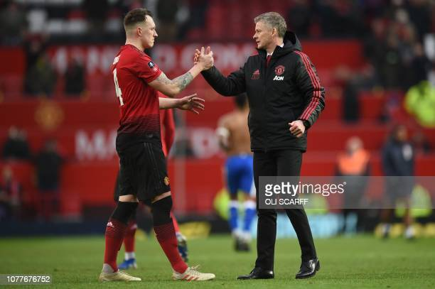 Manchester United's Norwegian caretaker manager Ole Gunnar Solskjaer greets Manchester United's English defender Phil Jones at the end of the English...