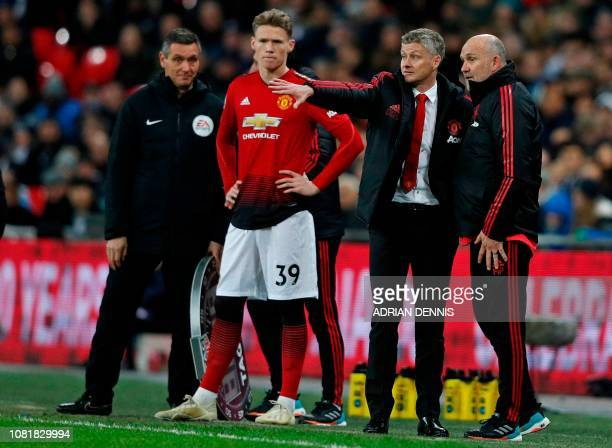 Manchester United's Norwegian caretaker manager Ole Gunnar Solskjaer discusses tactics with his training staff on the touchline during the English...
