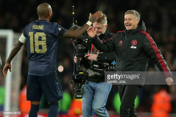 Manchester United's Norwegian caretaker manager Ole Gunnar Solskjaer celebrates with Manchester United's English midfielder Ashley Young on the pitch...