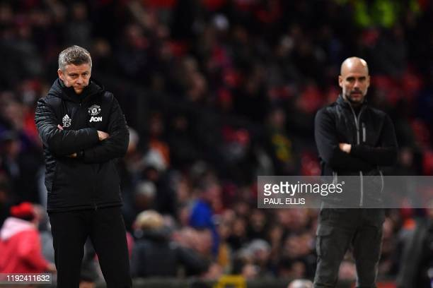 Manchester United's Norwegian manager Ole Gunnar Solskjaer and Manchester City's Spanish manager Pep Guardiola react during the English League Cup...