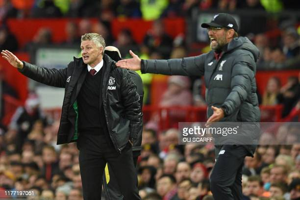 Manchester United's Norwegian manager Ole Gunnar Solskjaer and Liverpool's German manager Jurgen Klopp gesture on the touchline during the English...